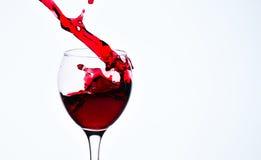 一块玻璃用红葡萄酒和浪花 库存图片