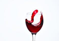 一块玻璃用红葡萄酒和浪花 免版税库存图片