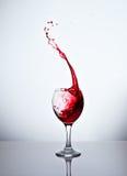 一块玻璃用红葡萄酒和浪花 免版税库存照片