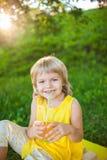 从一块玻璃的女孩饮用的汁液在草坪 库存图片
