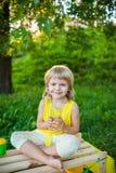 从一块玻璃的女孩饮用的汁液在草坪 免版税图库摄影