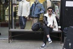一块黑皮夹克和橙色玻璃的年轻人抽烟和听的音乐,坐长凳在商店附近 免版税库存照片