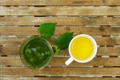 一块绿色汁液玻璃&一个茶杯在木桌上在庭院里 免版税图库摄影