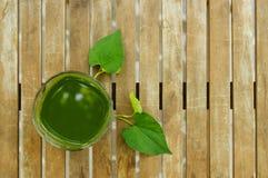 一块绿色汁液玻璃&叶子在木桌上在庭院里 免版税库存图片