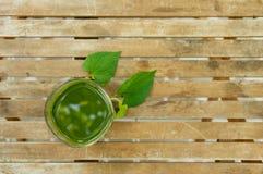 一块绿色汁液玻璃&叶子在木桌上在庭院里 库存图片