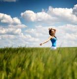 一块绿色麦田的愉快的无忧无虑的少妇 图库摄影