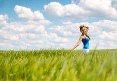一块绿色麦田的愉快的无忧无虑的少妇 免版税库存图片