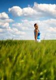 一块绿色麦田的愉快的无忧无虑的少妇 库存照片
