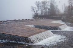 一处美好的挪威秋天风景 在湖的有薄雾的早晨 水漫过水坝的,瀑布 库存图片