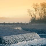 一处美好的挪威秋天风景 在湖的有薄雾的早晨 水漫过水坝的,瀑布 图库摄影
