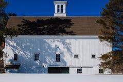 一多雪的领域aganst的大白色新英格兰谷仓深蓝色晚冬天空 免版税图库摄影
