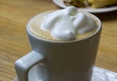 一大泡沫冠上了在一个简单的瓷杯子的热的热奶咖啡咖啡 免版税库存照片