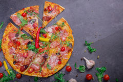 一大薄饼margherita用肉、乳酪和香料在深灰背景 在一张灰色桌上的很多菜 库存照片
