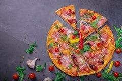 一大薄饼margherita用肉、乳酪和香料在深灰背景 在一张灰色桌上的很多菜 库存图片