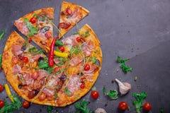 一大薄饼margherita用肉、乳酪和香料在深灰背景 在一张灰色桌上的很多菜 图库摄影