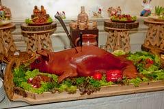 一头幼小整个,被烘烤的猪,说谎在一张欢乐桌上装饰用草本 免版税库存照片