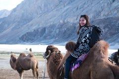 一头美丽的亚洲旅游妇女骑马骆驼在Hunder沙漠 免版税库存照片