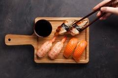 一套与三文鱼的寿司、虾和鳗鱼和木筷子在一个木板 在一黑暗的石backgr的可口日本食物 库存照片