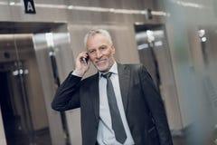 一套严密的衣服的一个可敬的年长人沿有一个电话的办公室走廊走在他的手、微笑和谈话上 库存照片