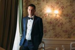 一套严密的衣服的典雅的新郎与一件白色衬衣和在常礼服的一个蝶形领结在一婚礼之日 商人 免版税图库摄影