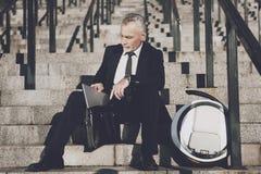 一套严密的西装的一个可敬的老人坐步办公室 他在片剂工作,在他的单音轮子旁边 免版税库存照片