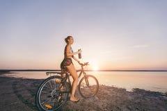 一套五颜六色的衣服的一名坚强的白肤金发的妇女在沙漠区域坐自行车,在水附近拿着黑瓶用水 fitne 免版税库存图片