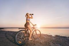 一套五颜六色的衣服的一名坚强的白肤金发的妇女坐自行车,在水附近喝从一个黑瓶的水在沙漠区域 Fi 免版税库存照片