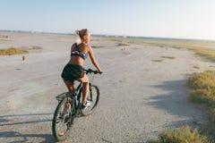 一套五颜六色的衣服的一名运动的白肤金发的妇女在一个晴朗的夏日在沙漠区域骑一辆自行车 球概念健身pilates放松 回到视图 图库摄影