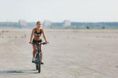 一套五颜六色的衣服的一名运动的白肤金发的妇女在一个晴朗的夏日在沙漠区域骑一辆自行车 球概念健身pilates放松 背景蓝天 免版税库存照片