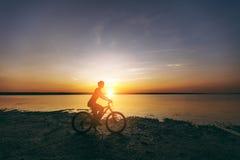 一套五颜六色的衣服的一名运动的白肤金发的妇女在水附近在沙漠区域骑一辆自行车在一个晴朗的夏日 球概念健身pilates放松 蓝色 库存图片