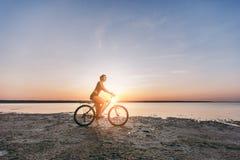 一套五颜六色的衣服的一名运动的白肤金发的妇女在水附近在沙漠区域骑一辆自行车在一个晴朗的夏日 球概念健身pilates放松 蓝色 免版税库存图片