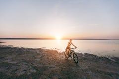 一套五颜六色的衣服的一名运动的白肤金发的妇女在水附近在沙漠区域骑一辆自行车在一个晴朗的夏日 球概念健身pilates放松 蓝色 库存照片