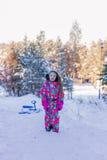 一套五颜六色的衣服的小女孩走在山的一个冬天森林里的 她乘坐sledging 免版税图库摄影