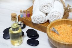 一套从芳香油、软的毛巾、热的石头和腌制槽用食盐的温泉做法在有一把匙子的一个木碗在一块白色大理石 免版税库存图片