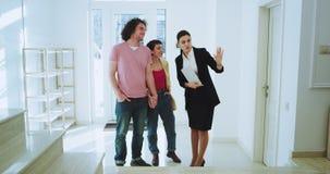 一套偶然衣服的房地产经纪人妇女显示一个大光亮房子为她客户美好已婚夫妇代理使用 股票视频