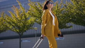 一套典雅的衣服的自信年轻女商人由机场终端在业务会议走进入 股票录像