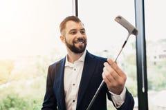 一套可敬的黑西装的一个人审查一家高尔夫俱乐部 关于与打高尔夫球的同事在办公室 库存图片