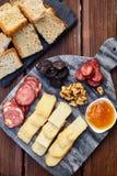 一套各种各样的乳酪、熏制的香肠、杏子橙色调味汁、核桃、血肠和炸面包在一个大理石委员会和向求爱 免版税库存照片