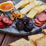 一套各种各样的乳酪、熏制的香肠、杏子橙色调味汁、核桃、血肠和炸面包在一个大理石委员会和向求爱 库存照片