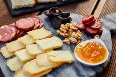 一套各种各样的乳酪、熏制的香肠、杏子橙色调味汁、核桃、血肠和炸面包在一个大理石委员会和向求爱 免版税库存图片