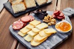 一套各种各样的乳酪、熏制的香肠、杏子橙色调味汁、核桃、血肠和炸面包在一个大理石委员会和向求爱 库存图片