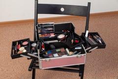 一套在一个手提箱箱子的专业化妆用品以在一把椅子的一种开放形式在有里面很多产品的秀丽演播室: 免版税库存图片