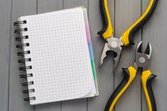 一套在一张木桌和一个空的笔记本上的工具为笔记 空的空间 库存图片