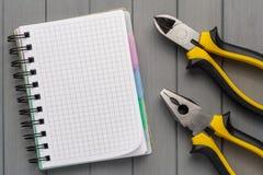 一套在一张木桌和一个空的笔记本上的工具为笔记 空的空间 库存照片