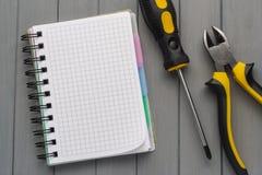 一套在一张木桌和一个空的笔记本上的工具为笔记 空的空间 免版税库存照片