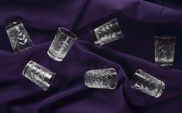 一套在紫罗兰色布料背景的玻璃 顶视图 免版税库存照片