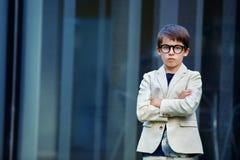 一套好的衣服和玻璃的小男孩 回到 免版税库存图片