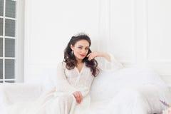 一套婚礼礼服的新娘与冠坐一个白色沙发 库存图片