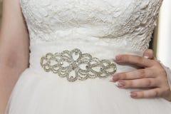一套婚礼礼服的片段与用宝石和珍珠装饰的传送带的 库存照片