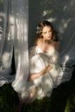 一套婚礼礼服的美丽的女孩在草 库存照片